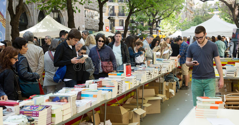 Books on street stalls in Barcelona. BARCELONA, SPAIN - APRIL 23, 2015: Books on street stalls in Barcelona, Catalonia. Books and red roses - symbols of Sant royalty free stock images