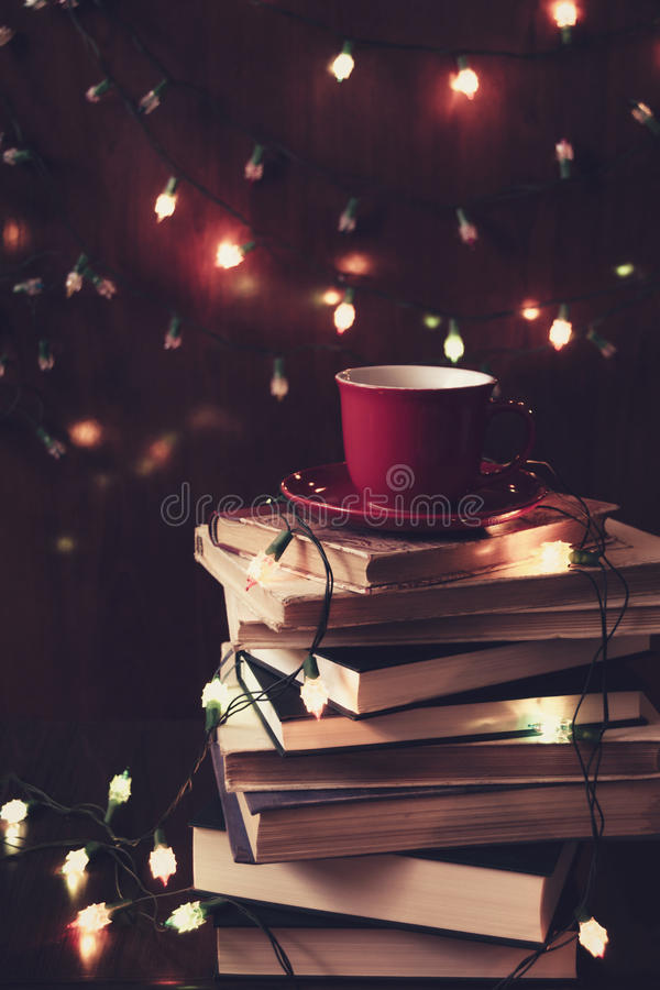 Books, tea and Christmas lights. Red cup of tea on a stack of books and Christmas lights in the background. Retro filter royalty free stock image