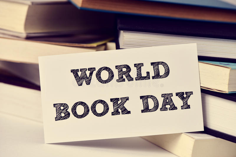 Books and text world book day. Closeup of a piece of paper with the text world book day in front of a pile of books, placed on a white surface stock photography