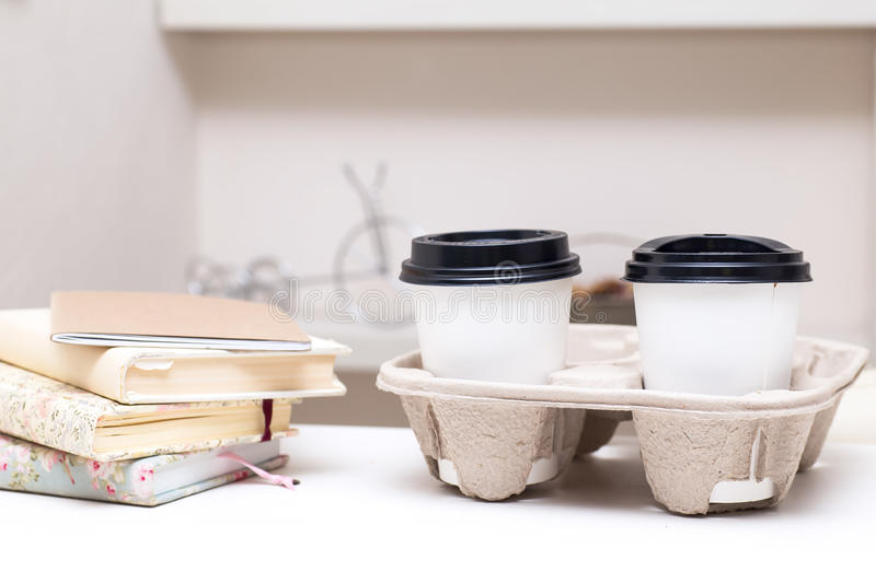 Books and two cardboard cups of coffee at the table stock image