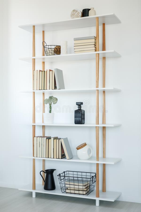 Books on white wooden shelves in simple living room interior. Re royalty free stock photography