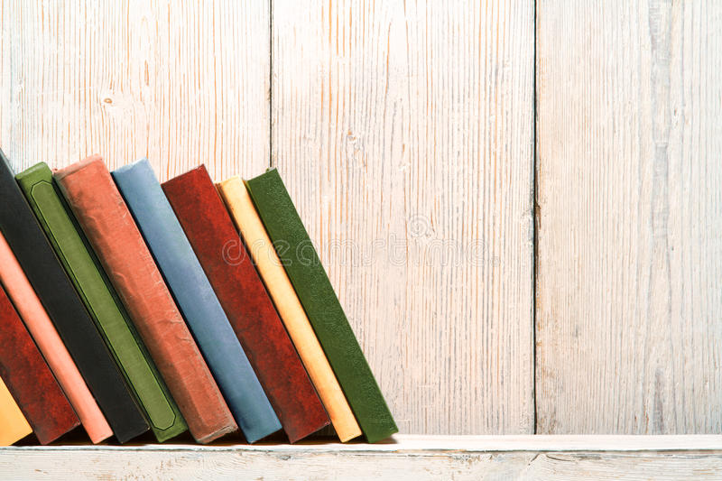 Books Wood Shelf, Old Spines Covers, White Wooden Wall. Books Wood Shelf, Old Spines Covers on White Vintage Wooden Wall Background royalty free stock image