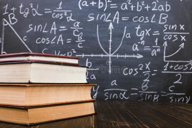 Books on a wooden table, against the background of a chalk board with formulas. Teacher's day concept and back to school royalty free stock images