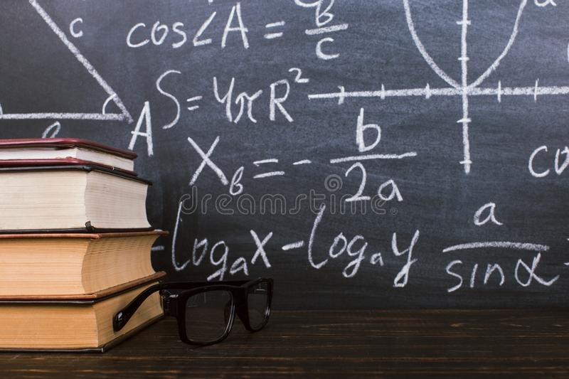 Books on a wooden table, against the background of a chalk board with formulas. Teacher's day concept and back to school stock images