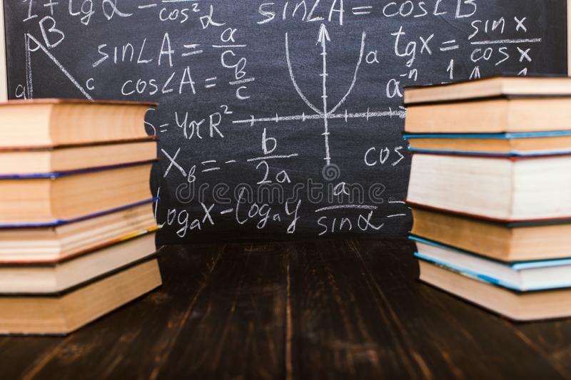 Books on a wooden table, against the background of a chalk board with formulas. Teacher's day concept and back to school. Books on a wooden table, against stock photos