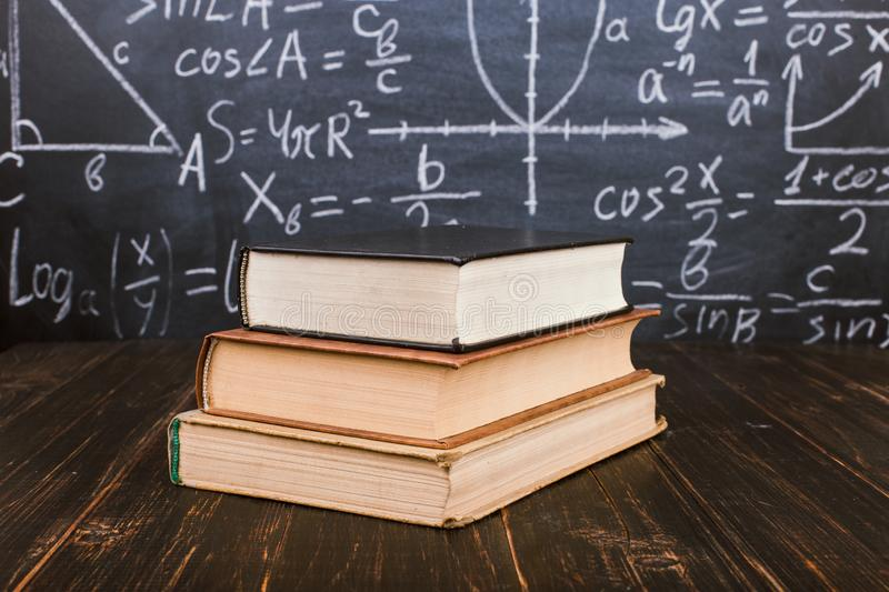 Books on a wooden table, against the background of a chalk board with formulas. Teacher's day concept and back to school. Books on a wooden table, against stock image