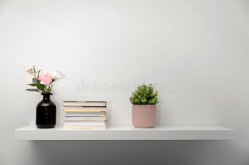Bookshelf on white wall with decorations. Wooden bookshelf on white wall with decorations stock image