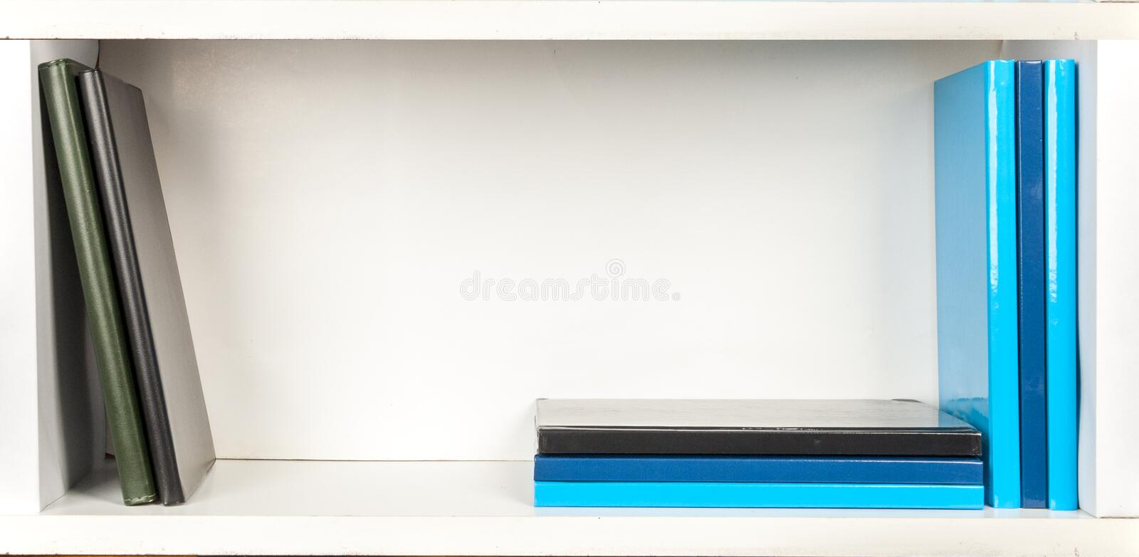 White bookshelf with few books. Bookshelf - colored grey, blue and black books on white shelfs royalty free stock image