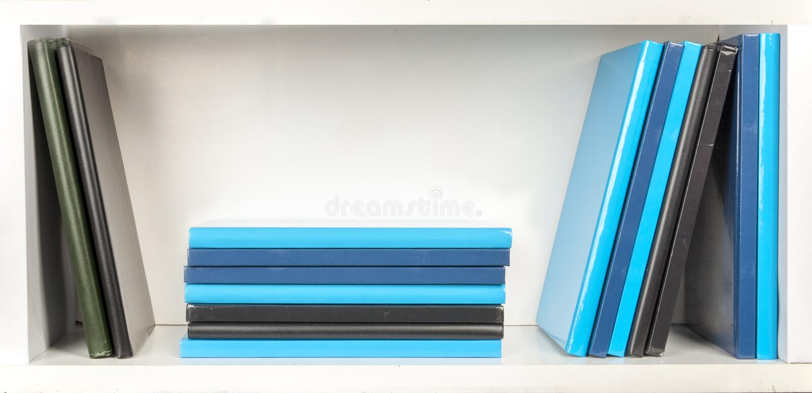 White bookshelf with few books. Bookshelf - colored grey, blue and black books on white shelfs stock image