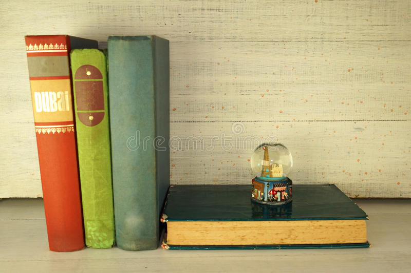 Bookshelf. A few old books stacked inside a rustic white wood bookshelf, a small ornament on top of one of them stock photography