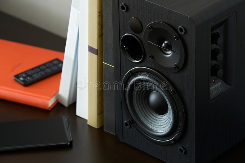 Bookshelf speaker. With books, smartphone and remote controller on a TV stand royalty free stock photo