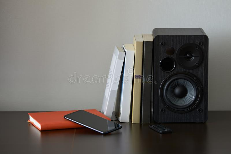 Bookshelf speaker. With books, smartphone and remote controller on a TV stand royalty free stock photos