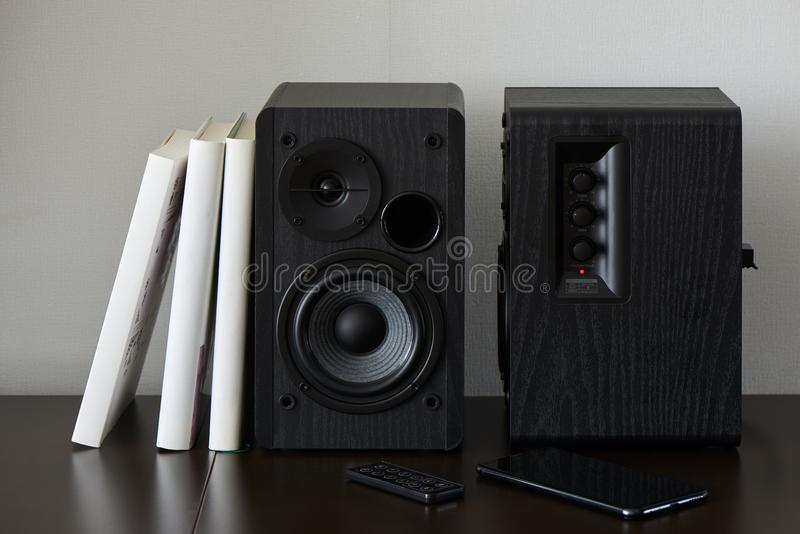 Bookshelf speakers. Bookshelf speaker with books, smartphone and remote controller on a TV stand stock photography