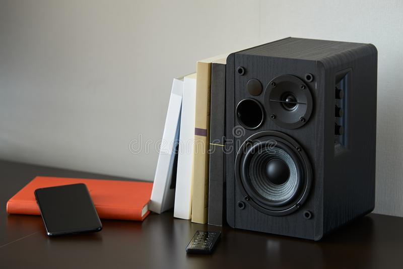 Bookshelf speaker. With books, smartphone and remote controller on a TV stand royalty free stock images