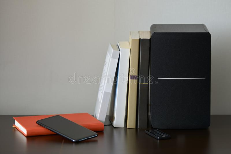 Bookshelf speaker. With books, smartphone and remote controller on a TV stand stock images