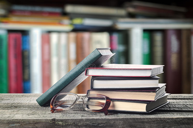 Bookshelf. Stack of books and glasses on wooden table with bookshelf, invitation to study literatures, close up, reading room stock photo