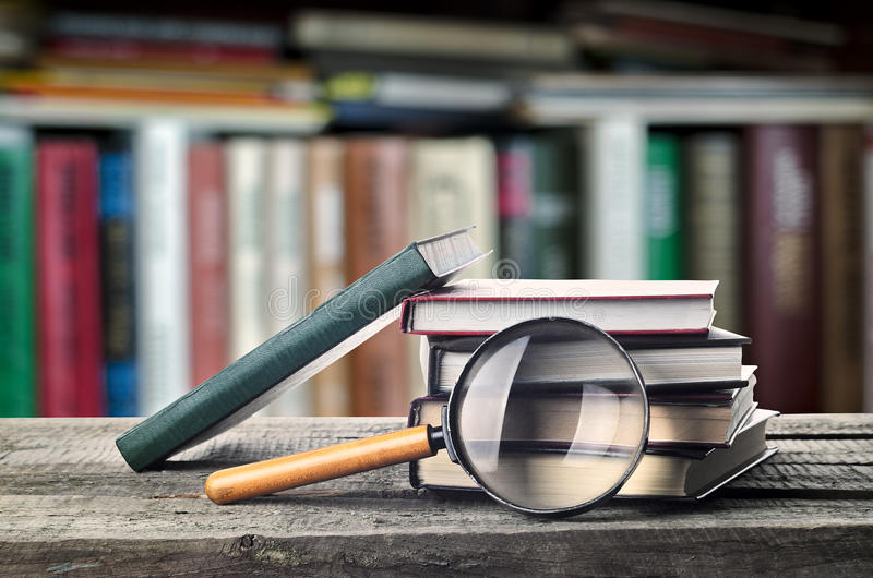 Bookshelf. Stack of books and magnifier on wooden table with bookshelf, invitation to study literatures, close up, reading room royalty free stock photography
