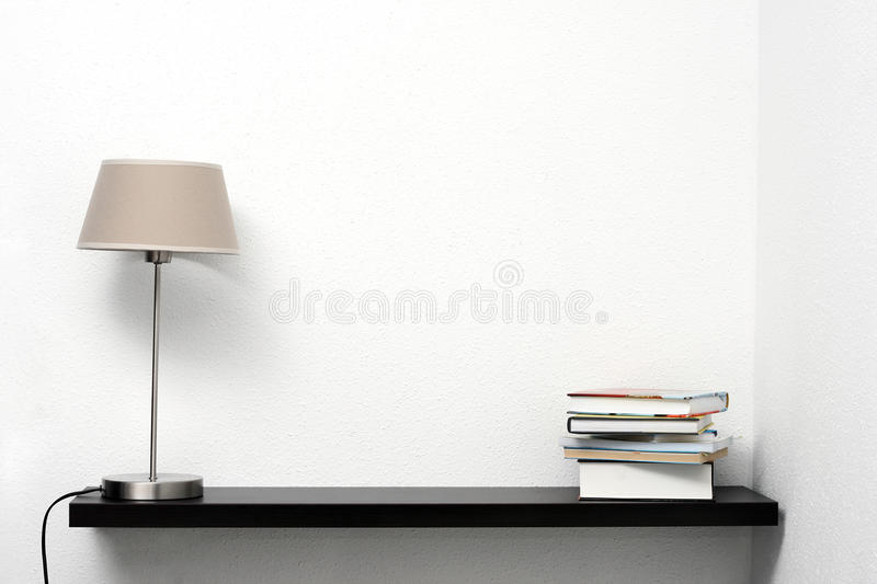 Bookshelf on the wall with lamp and books stock photography