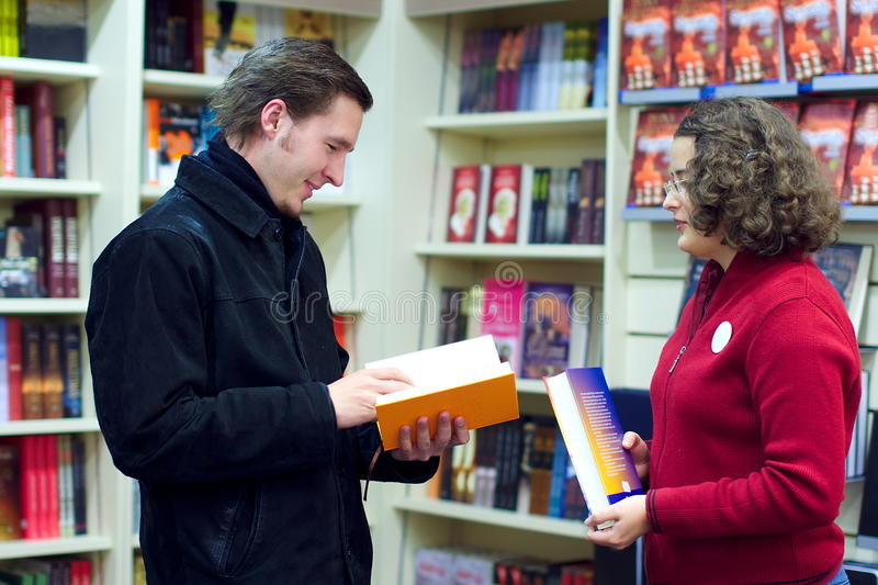 Bookshop assistant and the customer stock photos