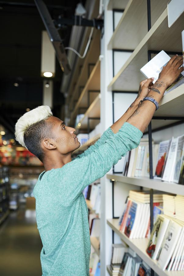 Bookstore employee putting books on shelf. Serious handsome young male bookstore employee with tattoos on arms standing at bookshelf and putting books on shelf royalty free stock photography