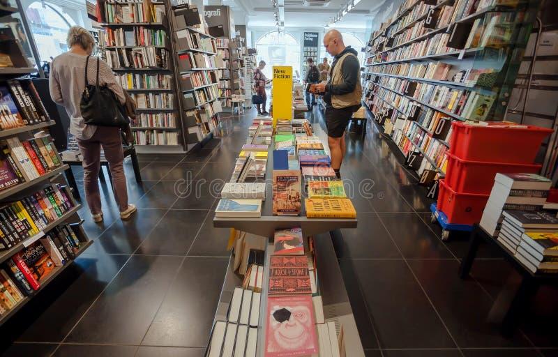 Bookstore klienci leaf przez nowego beletrystycznego książki inside nowożytnej księgarni fotografia stock