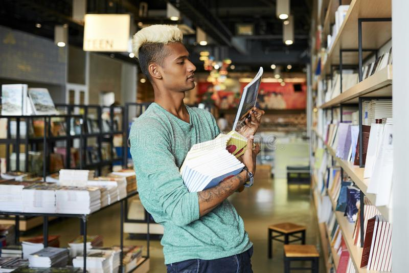 Bookstore manager doing inventory. Serious handsome young black bookstore manager with blond Mohawk holding stack of books and checking title of book while doing royalty free stock photo