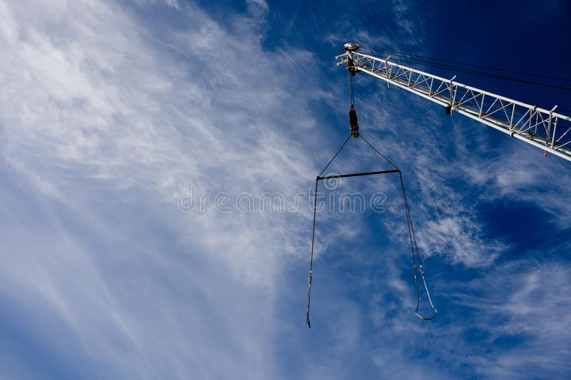 Boom crane with a cable against the blue sky. Background. Copy space royalty free stock images