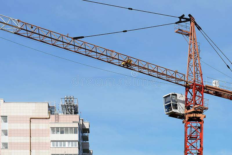 Boom crane on the construction of a high-rise building. Blue sky, high-rise building, construction, close-up, crane operator`s royalty free stock photos