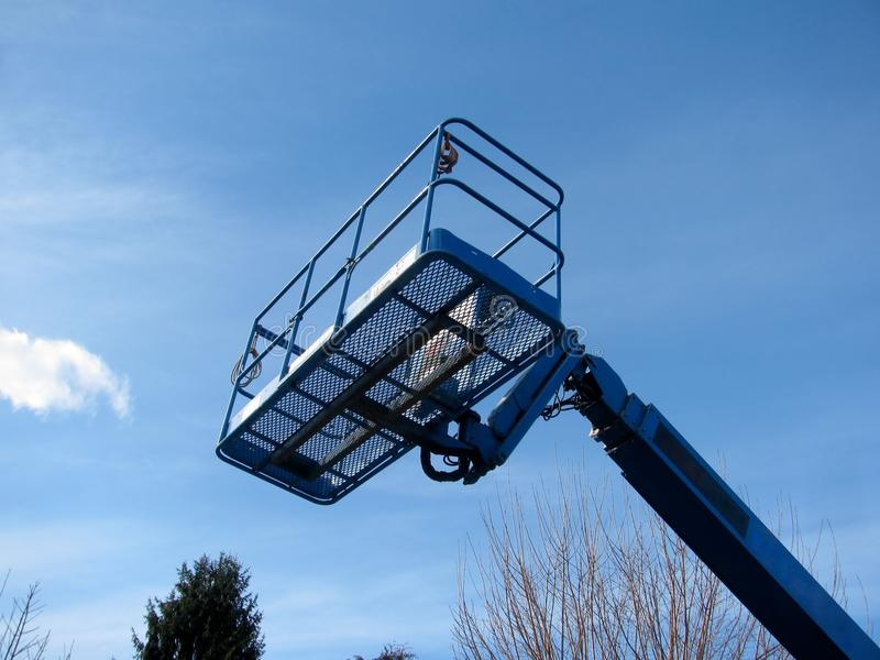 Boom lift reaching high up. Blue elevated work bucket platform. stock photos