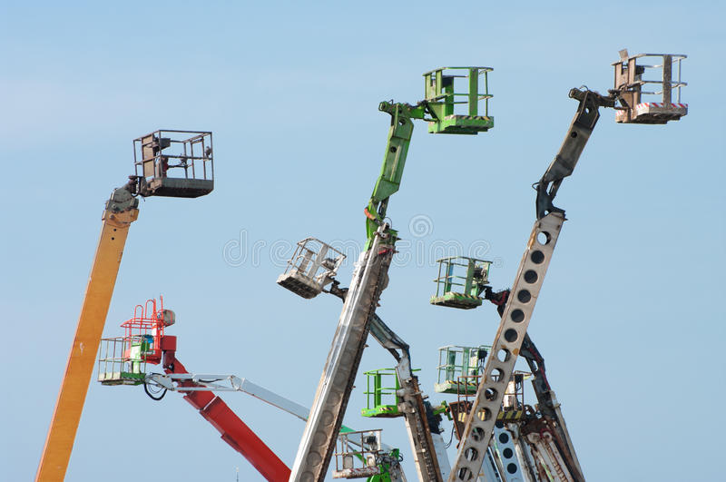Boom lifts. Several colored boom lifts with cages royalty free stock image