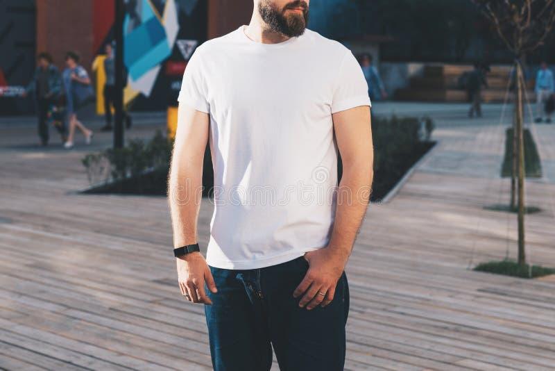 Boom op gebied De jonge gebaarde hipstermens gekleed in witte t-shirt en zonnebril is tribunes op stadsstraat Spot omhoog stock afbeeldingen
