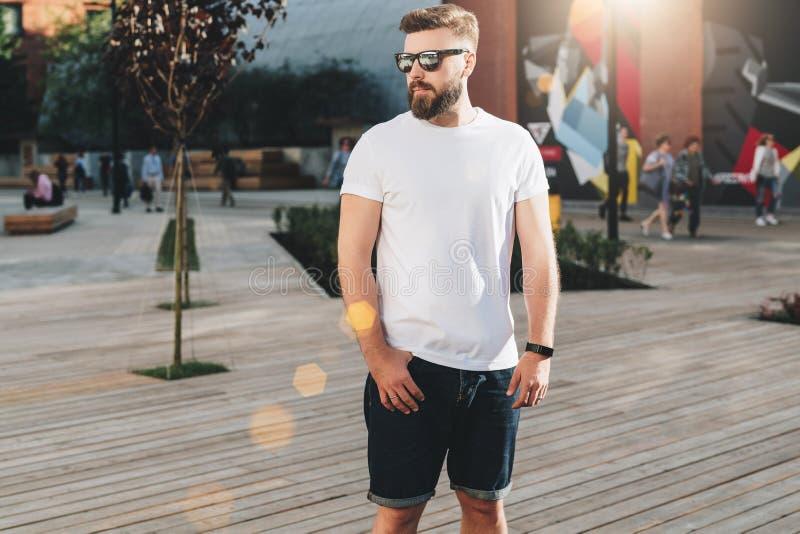 Boom op gebied De jonge gebaarde hipstermens gekleed in witte t-shirt en zonnebril is tribunes op stadsstraat Spot omhoog royalty-vrije stock fotografie