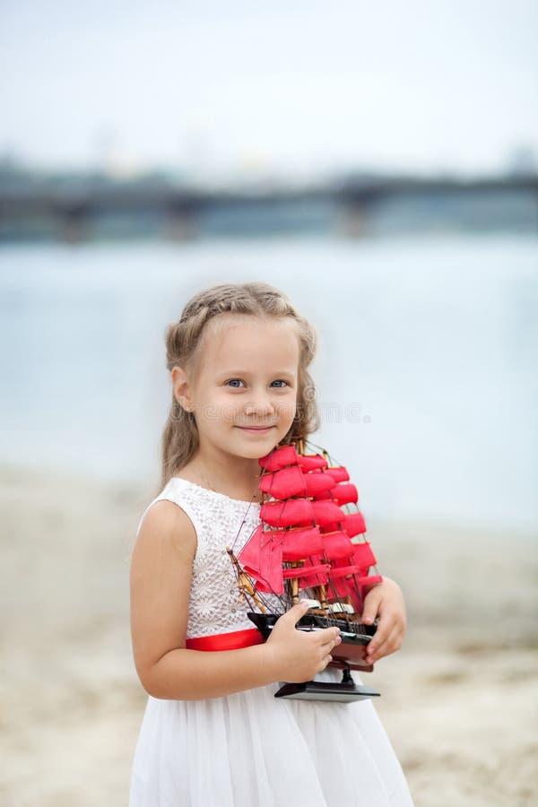 Boom op gebied Gelukkig kinderjaren onbezorgd spel op het open zand Het concept rust Meisje op het overzees met een schip Close-u royalty-vrije stock foto's