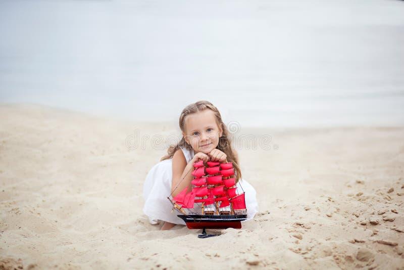 Boom op gebied Gelukkig kinderjaren onbezorgd spel op het open zand Het concept rust Meisje op het overzees met een schip Portret royalty-vrije stock foto