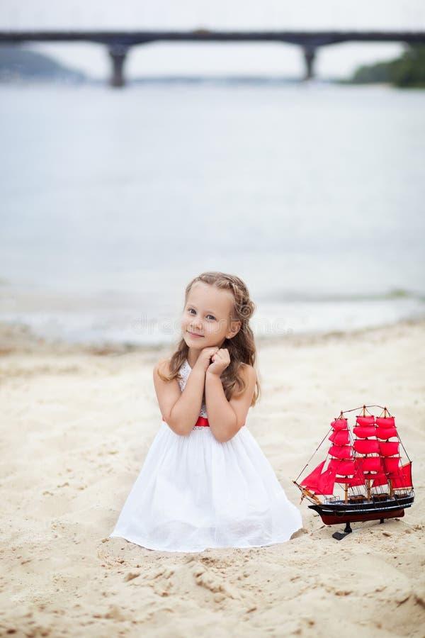 Boom op gebied Gelukkig kinderjaren onbezorgd spel op het open zand Het concept rust Meisje op het overzees met een schip Portret stock fotografie