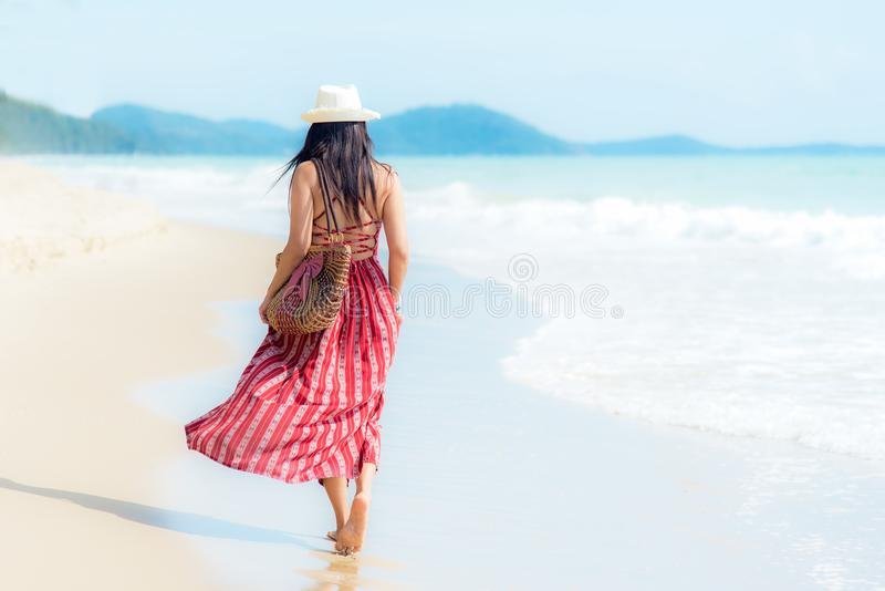 Boom op gebied Glimlachende vrouw die de manierzomer dragen die op het zandige oceaanstrand lopen De gelukkige vrouw geniet en on stock fotografie