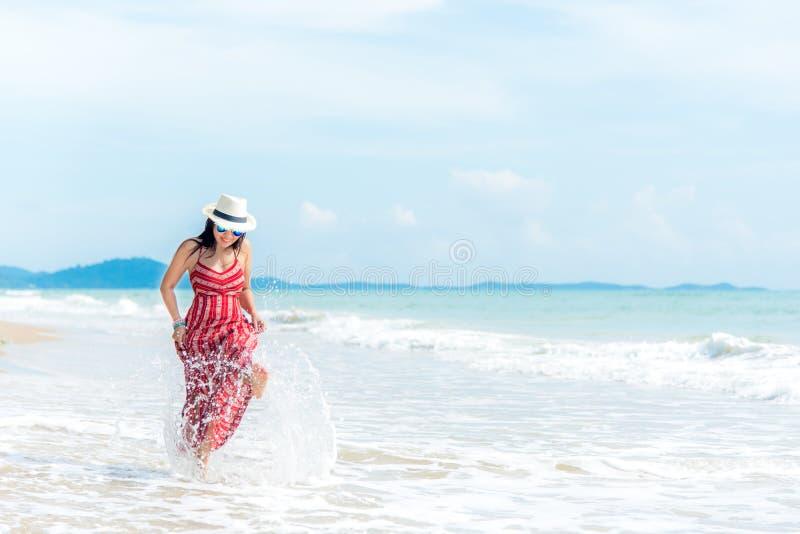 Boom op gebied Glimlachende vrouw die het strand dragen die van de manierzomer pret het spelen bespattend water hebben stock foto's