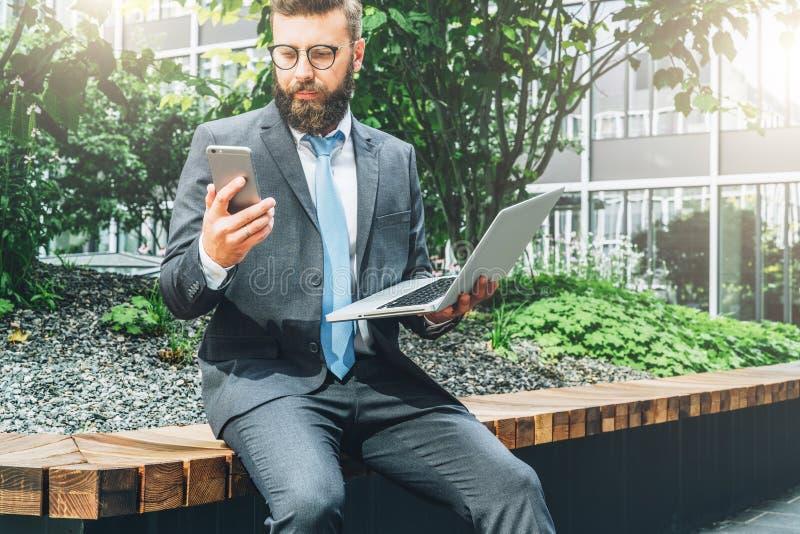 Boom op gebied Jonge gebaarde zakenman in kostuum en bandzitting in park op bank, holdingslaptop en het gebruiken van smartphone stock fotografie
