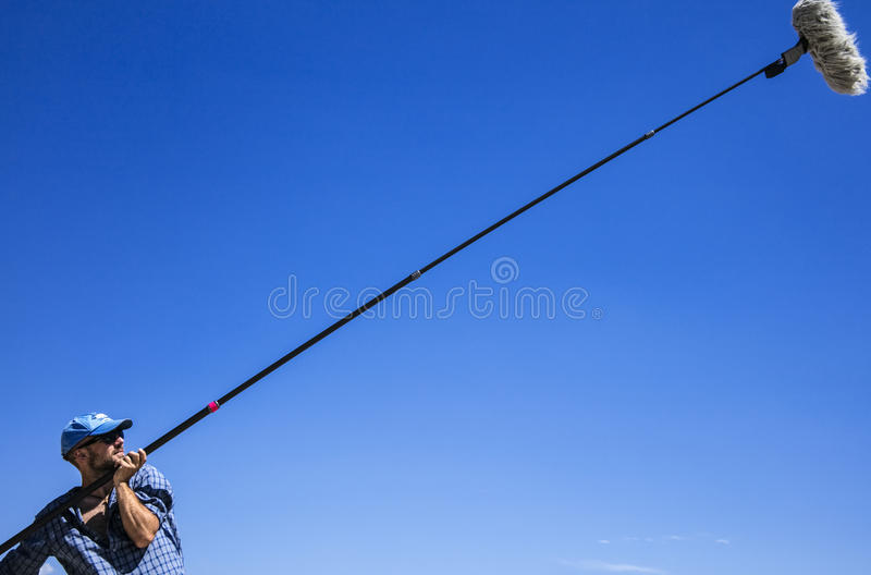 Boom operator at work. In the true blue sky background royalty free stock photos