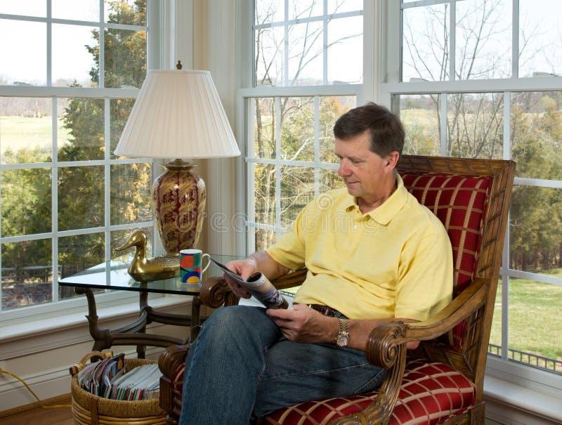 Boomer affichant un magazine par le jardin images stock