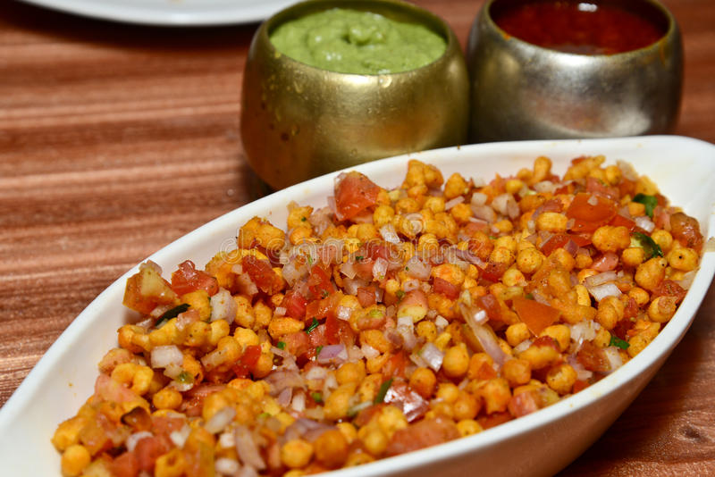 Boondi Chat. Spicy snack prepared from fried boondi,potatoes and garnished with sweet/sour sauce and Onions. A common street snack in Northern India stock photo