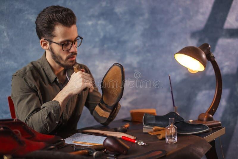 Boootmaker réparant la fermeture éclair dans les chaussures photos libres de droits
