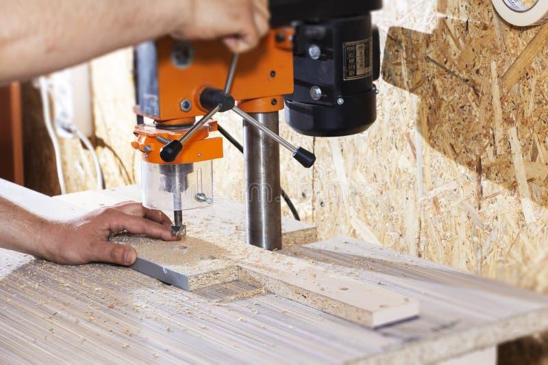 Boor in de boringsmachine, die meubilair maken stock afbeelding