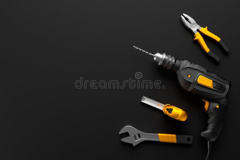 Boor, moersleutel en bouwhulpmiddelen op de zwarte achtergrond stock fotografie