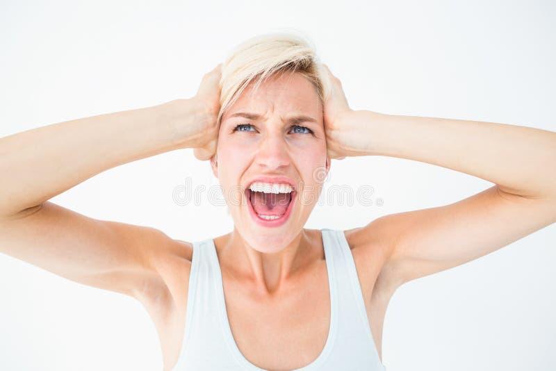 Boos blonde die en haar hoofd gillen houden royalty-vrije stock foto's