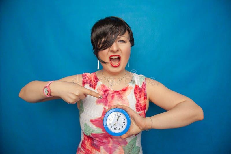 Boos gillend ongelukkig meisje die een ronde wekker op blauwe studioachtergrond houden stock afbeelding