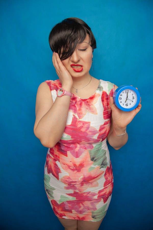 Boos gillend ongelukkig meisje die een ronde wekker op blauwe studioachtergrond houden stock foto's