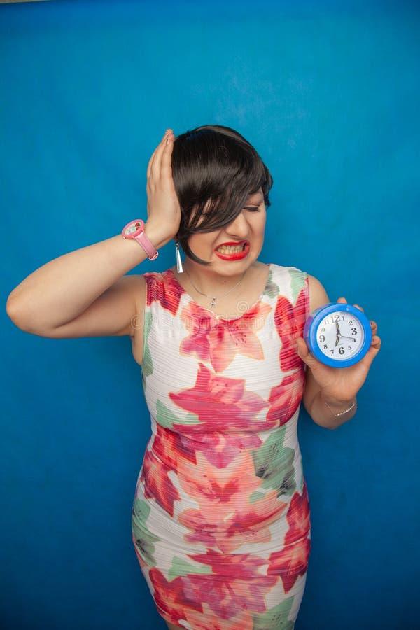 Boos gillend ongelukkig meisje die een ronde wekker op blauwe studioachtergrond houden royalty-vrije stock fotografie
