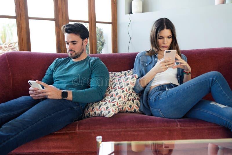 Boos jong paar die elkaar negeren die telefoon na een argument met behulp van terwijl thuis het zitten op bank stock afbeelding