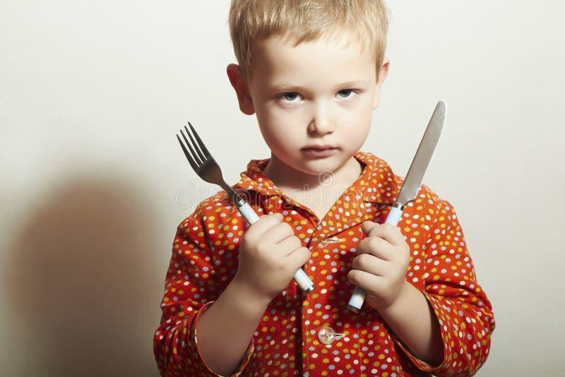 Boos kind hongerig weinig jongen met Vork en Mes Voedsel Wil eten royalty-vrije stock afbeelding